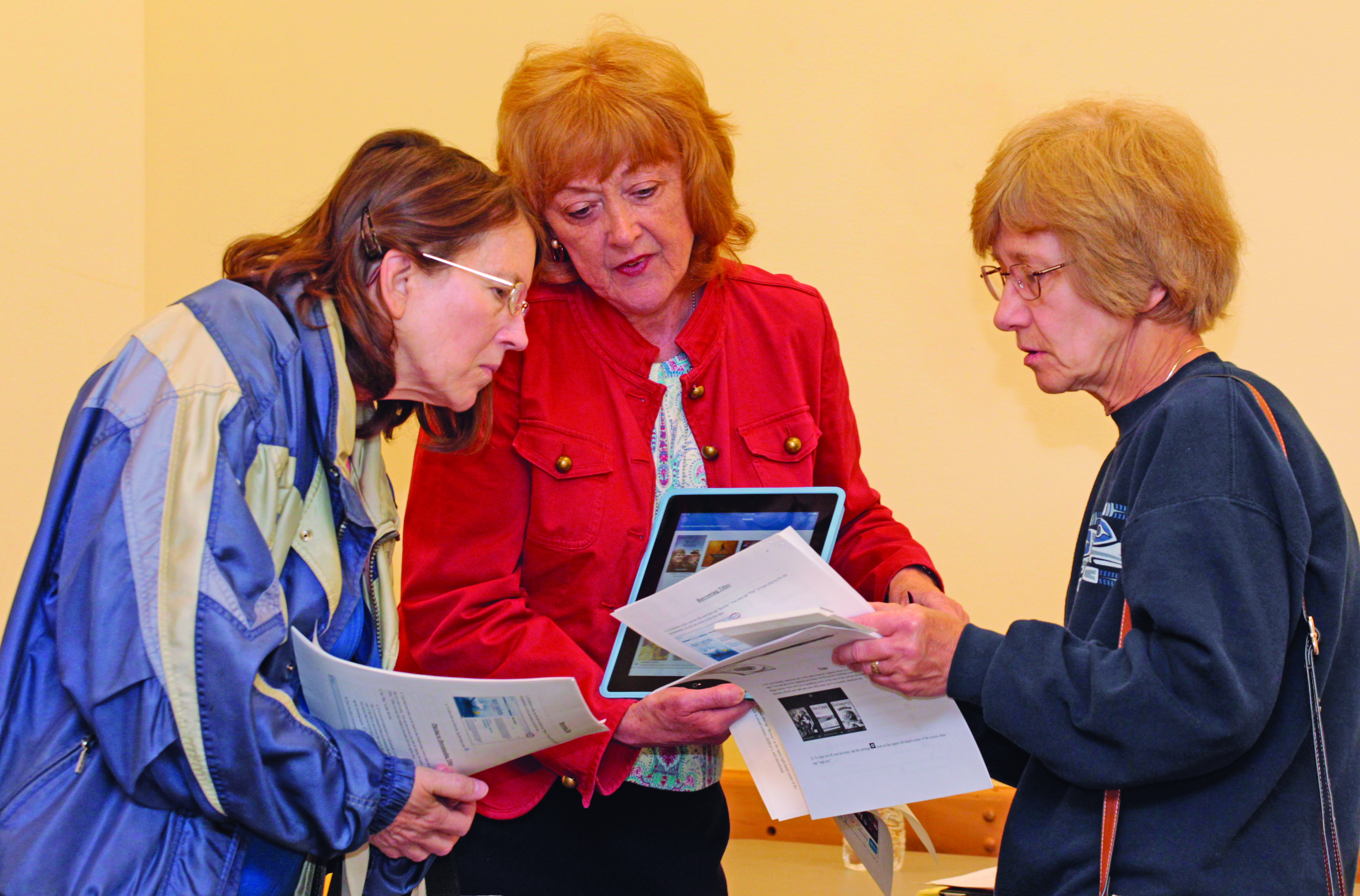 """Adult Services Librarian Karen Shalt demonstrates the """"Hoopla"""" app to Marcia Kline and Ginny Zajac. Photo by Chuck LeClaire"""